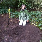Volunteer with freshly dug hole waiting for the new sapling to be planted.
